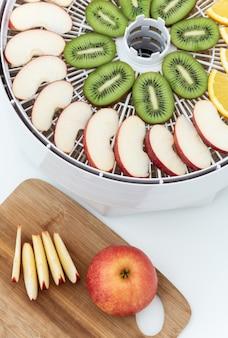 Dehydratorbakje met plakjes kiwi, appels en sinaasappels. vlakbij is er een snijplank met plakjes en een appel.