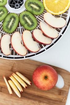 Dehydratorbakje met plakjes kiwi, appels en sinaasappels