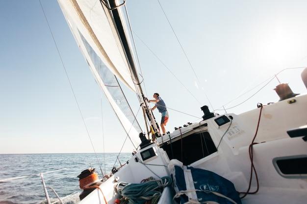 Dek van professionele zeilboot of racejacht tijdens wedstrijd op zonnige en winderige zomerdag, snel bewegend door golven en water, met spinnaker omhoog