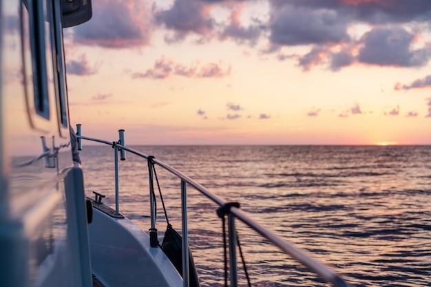 Dek van wit jacht zeilen in open zee bij zonsondergang
