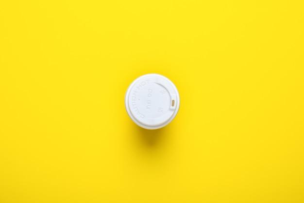 Deksel op een kartonnen glas van bovenaf op een gele.