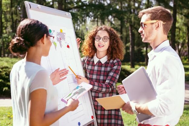 Delen met vrienden. alert curly-haired meisje presenteert haar project en haar vrienden die naar haar luisteren