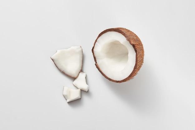 Delen van verse natuurlijke organische tropische vruchten kokosnoot op een lichtgrijze achtergrond met kopie ruimte. vegetarisch concept.