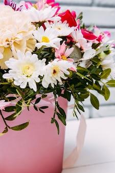 Delicaat boeket van verschillende bloemen in roze verpakking.