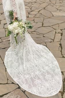 Delicaat boeket van witte pioenrozen in handen van de bruid