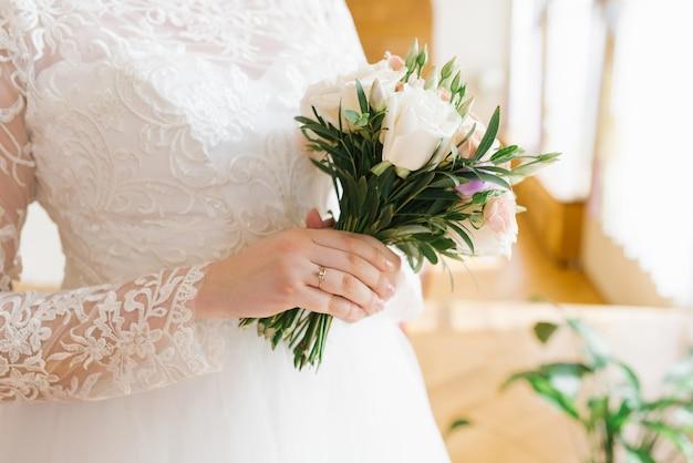 Delicaat mooi stijlvol boeket in de handen van de bruid een verlovingsring wordt gedragen