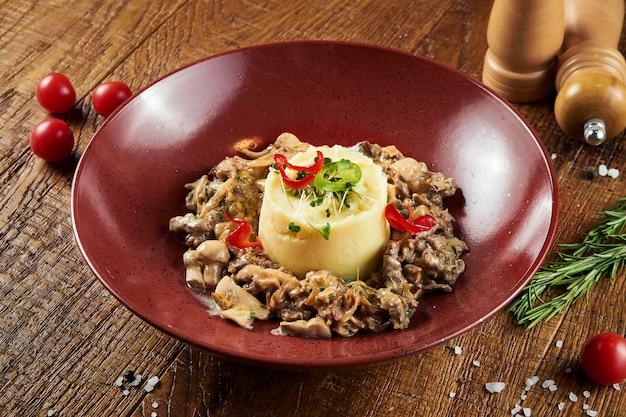 Delicate aardappelpuree met beef stroganoff in rode kom in een compositie met kruiden op houten oppervlak. restaurant eten. detailopname