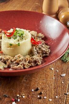 Delicate aardappelpuree met beef stroganoff in rode kom in een compositie met kruiden op restaurant eten. detailopname