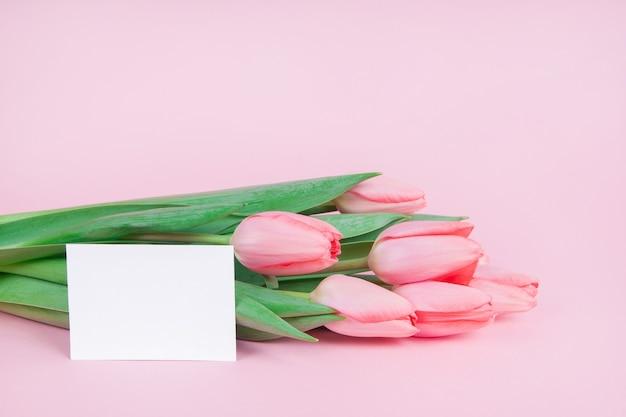 Delicate ansichtkaart bloemen tulpen met een notitie op een roze achtergrond mock-up