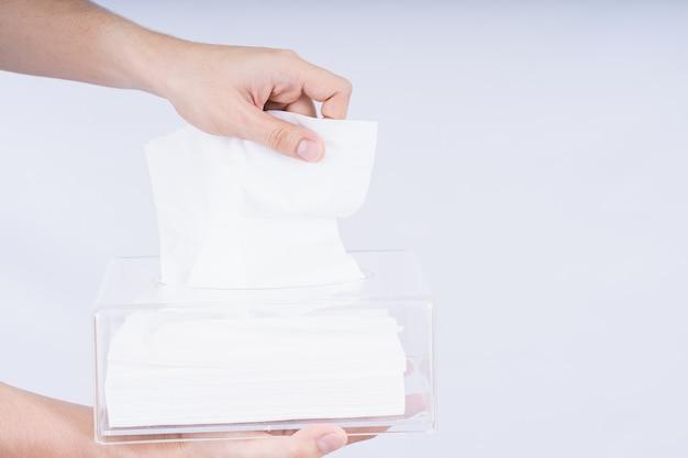 Delicate mannelijke handen die een wit tissuepapier uit een transparante doos van kristalweefsel trekken