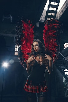 Delicate mooie brunette vrouw poseren met rode donkere engelenvleugels. studio-opname.