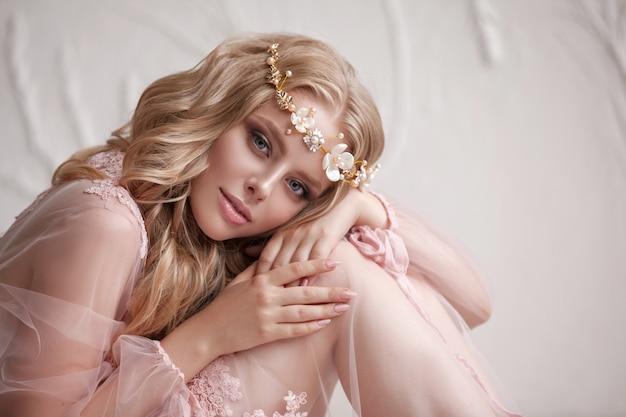 Delicate portret van een jong model meisje. het beeld van de bruid, een lichte kanten jurk in roze, een mooi kapsel en een natuurlijke make-up.