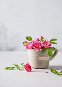 Delicate roze mini-roosjes in een klein kopje in beige kleur