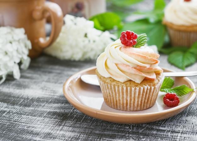 Delicate vanille cupcakes met room en frambozen op een donkere houten ondergrond