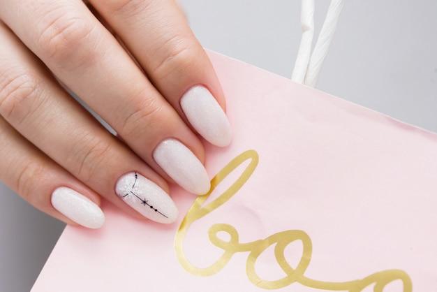 Delicate vrouwen manicure op een lichte papieren zak.