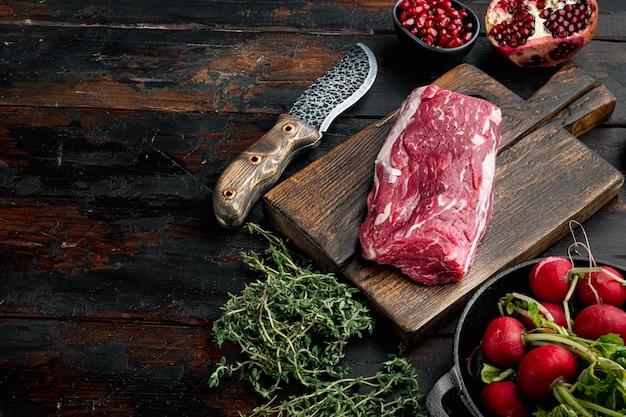 Delicatessen voorgerecht van vers vlees - rundercarpaccio rauwe verse ingrediënten set, op oude donkere houten tafel