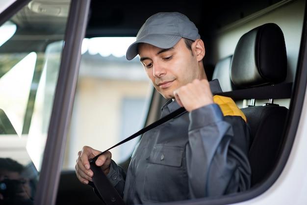 Deliverer die de veiligheidsriem op zijn busje zet
