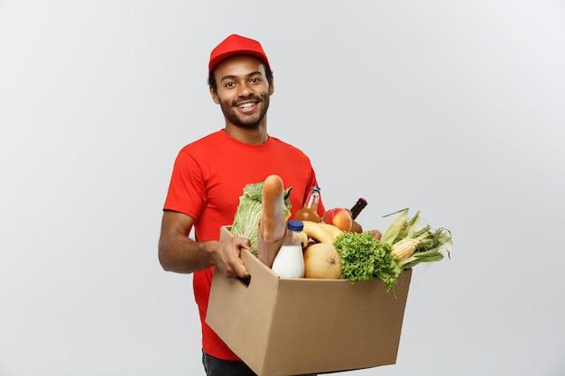 Delivery concept - knappe afro-amerikaans leveringsman met een pakket doos met kruidenierswinkel eten en drinken uit de winkel. geïsoleerd op grijze studio achtergrond. ruimte kopiëren.