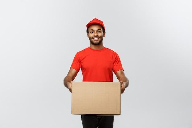 Delivery concept - portret van gelukkige afro-amerikaanse levering man in blauwe doek lopen om een doos pakket naar de klant te sturen. geïsoleerd op grijze studio achtergrond. ruimte kopiëren.