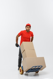 Delivery concept - portret van knappe afro-amerikaanse leverancier of koerier duwen handwagen met stapel dozen. geïsoleerd op grijze studio achtergrond. ruimte kopiëren.