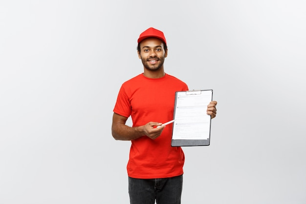 Delivery concept - portret van knappe afro-amerikaanse leveringsman of koerier met een bevestigingsdocumentformulier om te ondertekenen. geïsoleerd op grijze studio achtergrond. ruimte kopiëren.