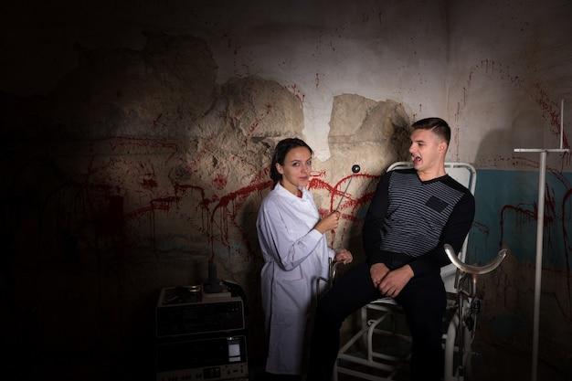 Demente wetenschapper met ijzeren medisch hulpmiddel voor schreeuwende patiënt in kerker met bloedige muren in een halloween-horrorconcept
