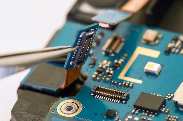 Demontage van smartphone die binnen elektrisch raad toont. de telefoon is aan het bevestigen