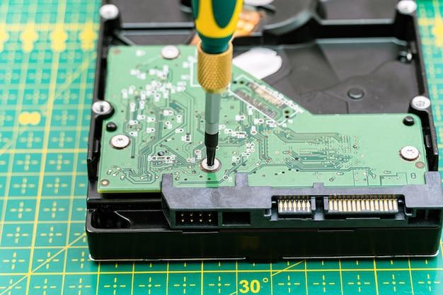Demontageproces van de harde schijf met schroevendraaier bij informatieherstel, reparatie hdd-service