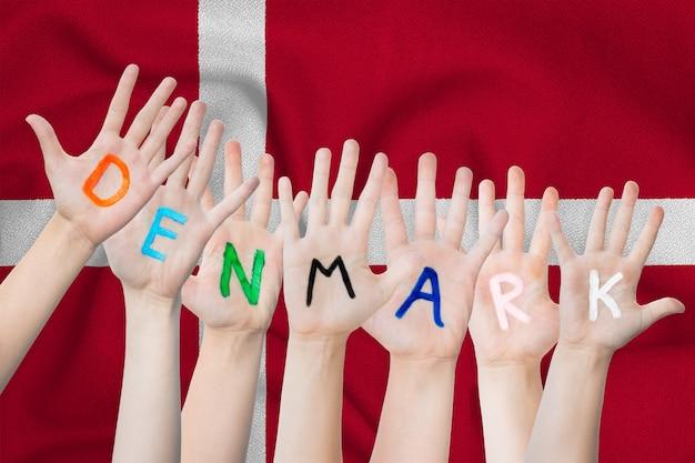 Denemarken inscriptie op de handen van de kinderen tegen de achtergrond van een wuivende vlag van denemarken