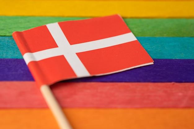 Denemarken vlag op regenboog achtergrond vlag symbool van lgbt gay pride maand sociale beweging regenboogvlag is een symbool van lesbiennes, homo's, biseksuelen, transgenders, mensenrechten, tolerantie en vrede.