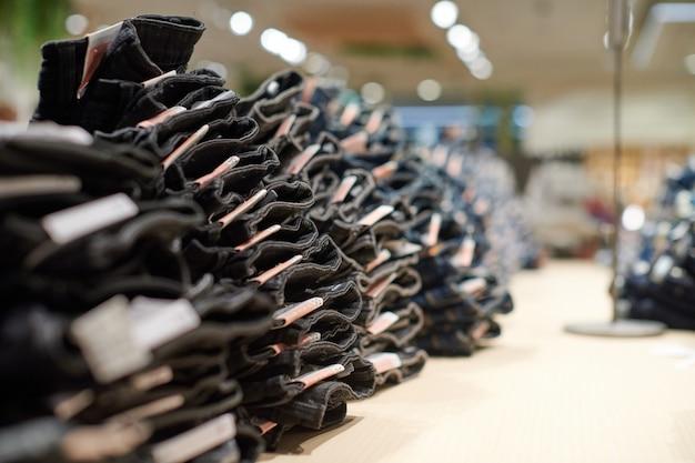 Denim jeans stapel op houten tafel bovenop in kledingwinkel in modern winkelcentrum shopping
