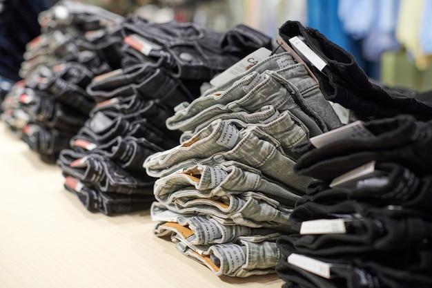 Denim jeans stapel op houten tafel bovenop in kledingwinkel in modern winkelcentrum shopping Premium Foto
