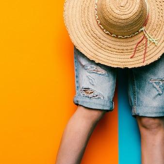 Denim shorts en strohoed. minimalistische stijl stedelijke mode
