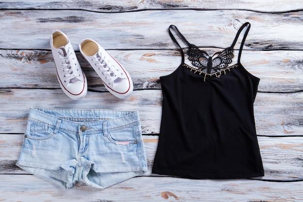 Denim shorts en zwarte top tanktop shorts en schoenen vrouwelijke outfit met donkere top kleding en cas...