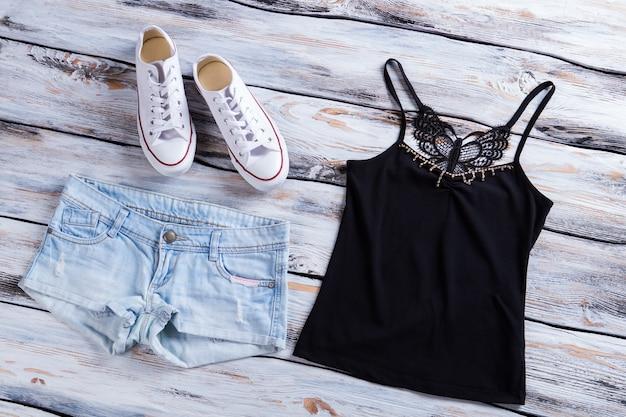 Denim shorts met donkere top zwarte top en canvas schoenen lichte denim shorts op tafel vrouwelijke kleding fr...