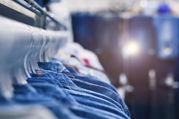 Denimoverhemden hangen aan hangers op een rij. kledingwinkel. stijl