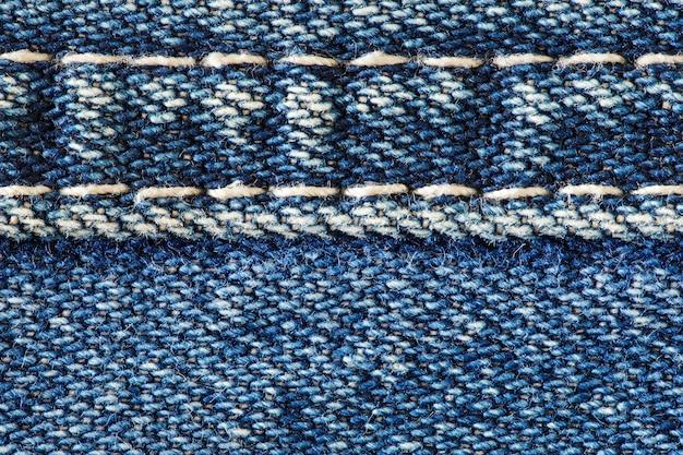 Denimstof met naad genaaid witte draden, close-up macroweergave