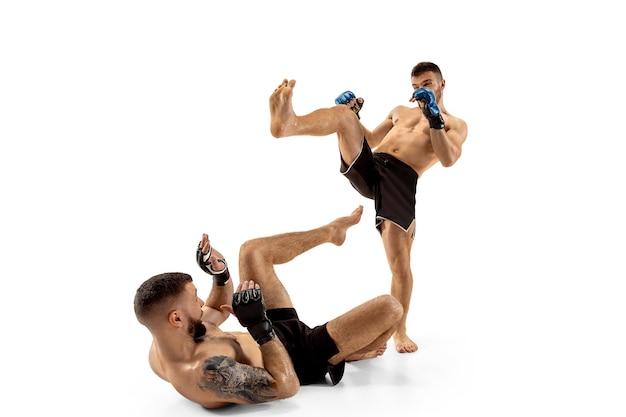 Denk aan bescherming. twee professionele vechters poseren geïsoleerd op een witte studio achtergrond. paar fit gespierde blanke atleten of boksers vechten. sport, competitie en menselijke emoties concept.