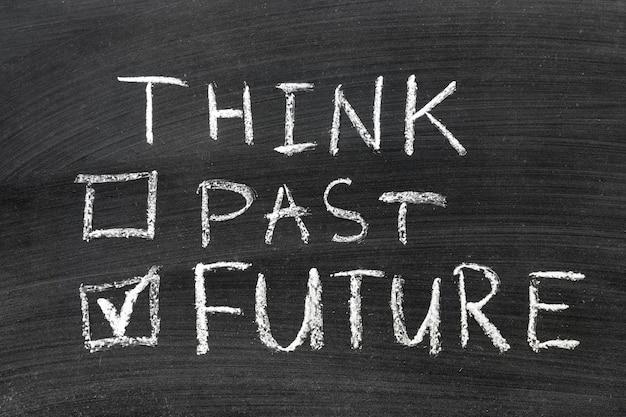 Denk aan toekomst, niet in het verleden, met de hand geschreven op het schoolbord