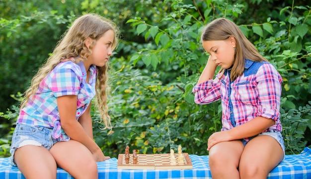 Denk beter. kleine meisjes schaken. zusters aan het schaken. slimme kinderen. ontwikkeling in de vroege kinderjaren. intellectueel spel. kinderen spelen schaak buitenshuis natuur achtergrond. sport- en hobbyconcept.