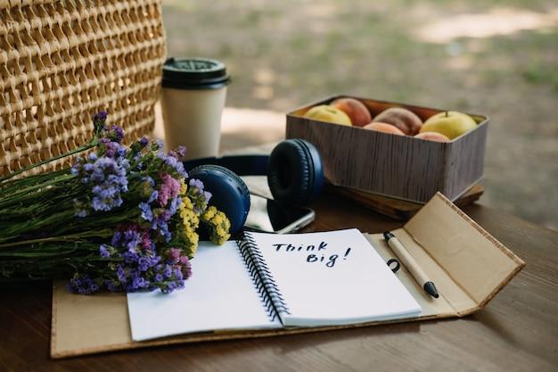Denk grote motiverende zin in open notitieboekje op tafel buiten stilleven met denk groot