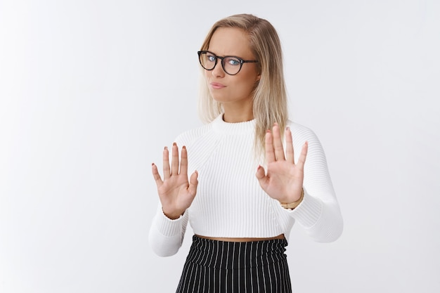 Denk het niet. ontevreden en weerzinwekkende intense zakenvrouw met een bril keert terug en keert zich af van afkeer en afkeer met opgeheven handpalmen in stop en weigering, een onuitsprekelijk aanbod afwijzend.