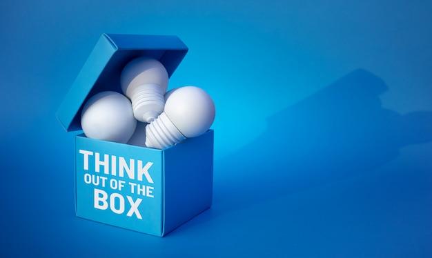 Denk out of the box concepten met gloeilamp in doos.