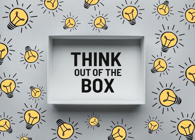 Denk out of the box-concepten met tekst in doos en gloeilampentekening