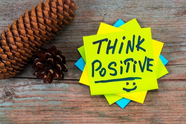Denk positief - inspirerend handschrift in een groene plaknotitie en dennenappels op houten achtergrond.