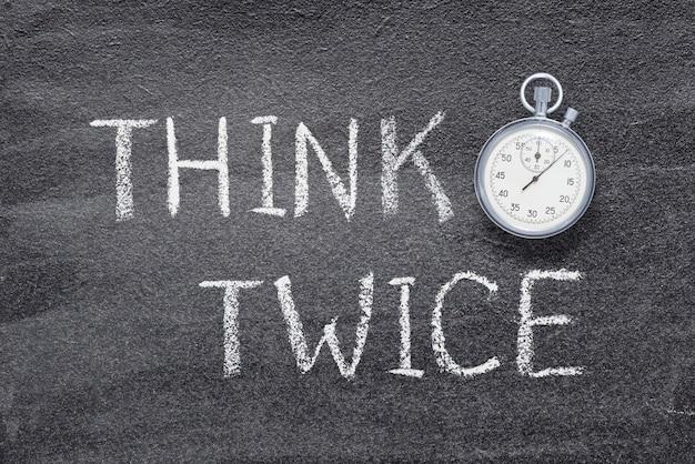 Denk twee keer zin geschreven op schoolbord met vintage nauwkeurige stopwatch