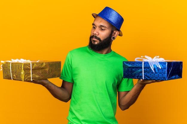 Denken aan een jonge afro-amerikaanse man met een feesthoed die vasthoudt en kijkt naar geschenkdozen geïsoleerd op een oranje muur