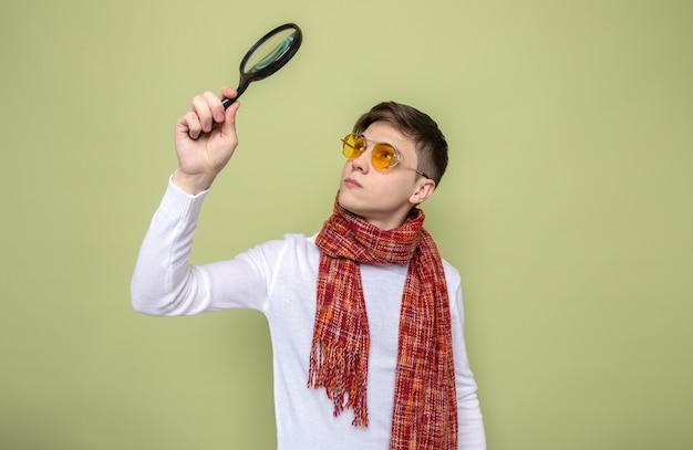 Denken aan een jonge knappe man met een sjaal met een bril die een vergrootglas vasthoudt en kijkt op een olijfgroene muur