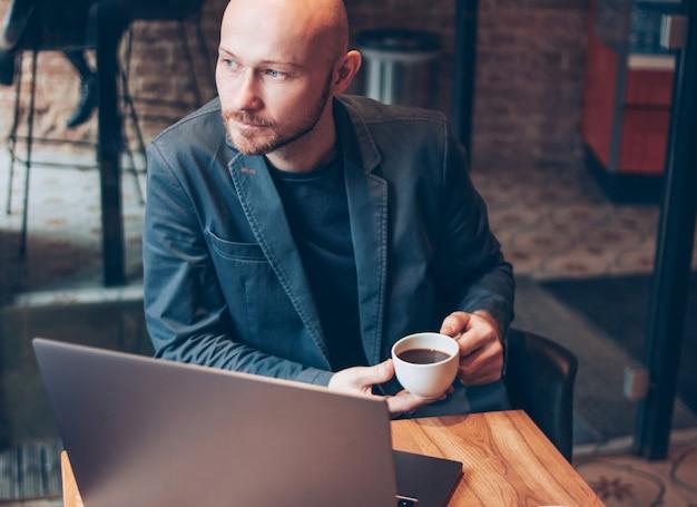 Denken aantrekkelijke volwassen succesvolle kale bebaarde man in pak met laptop in café