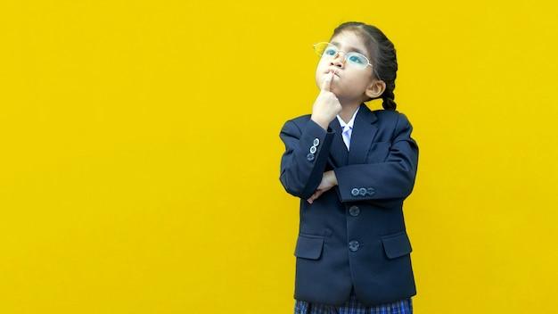Denken aziatische schoolkinderen met zakelijke formele uniform op gele geïsoleerde achtergrond